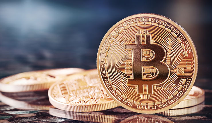 Golden Bitcoins with one standing on edge